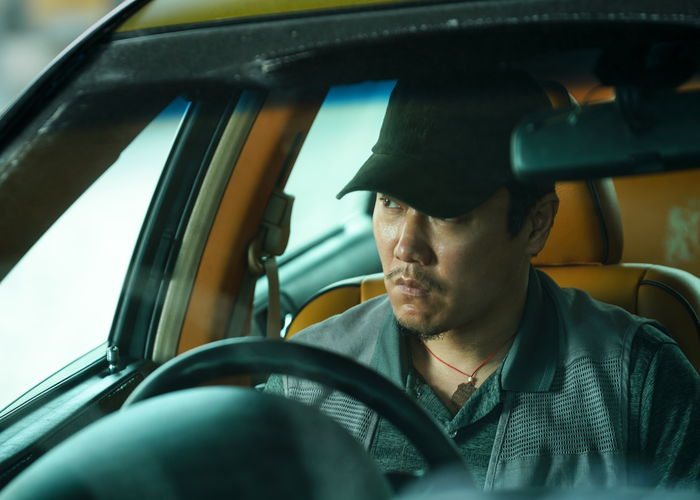 A man sits in a car looking out the front window driver's seat