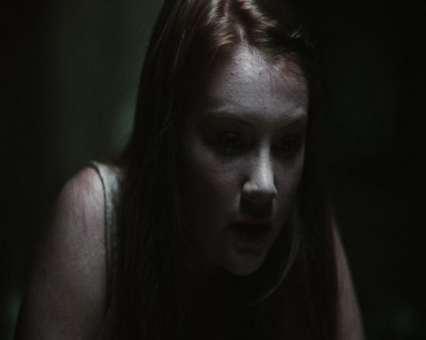 A woman stares down in a very dark room