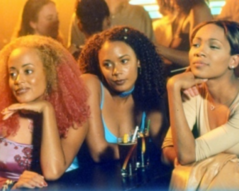A still from Love Song. Three women sit at a table with drinks