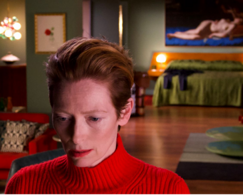 Tilda Swinton stands in a red jumper looking pensive