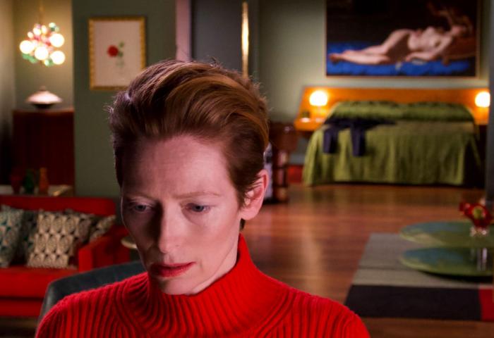 Tilda Swinton stands in a red jumper looking pensive