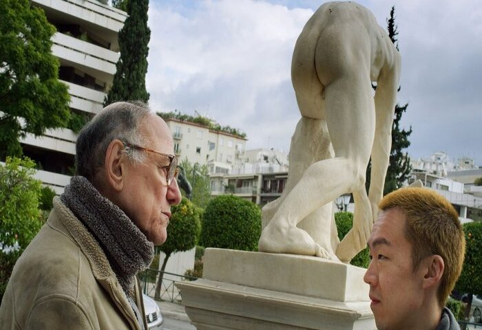two men stand by a statue